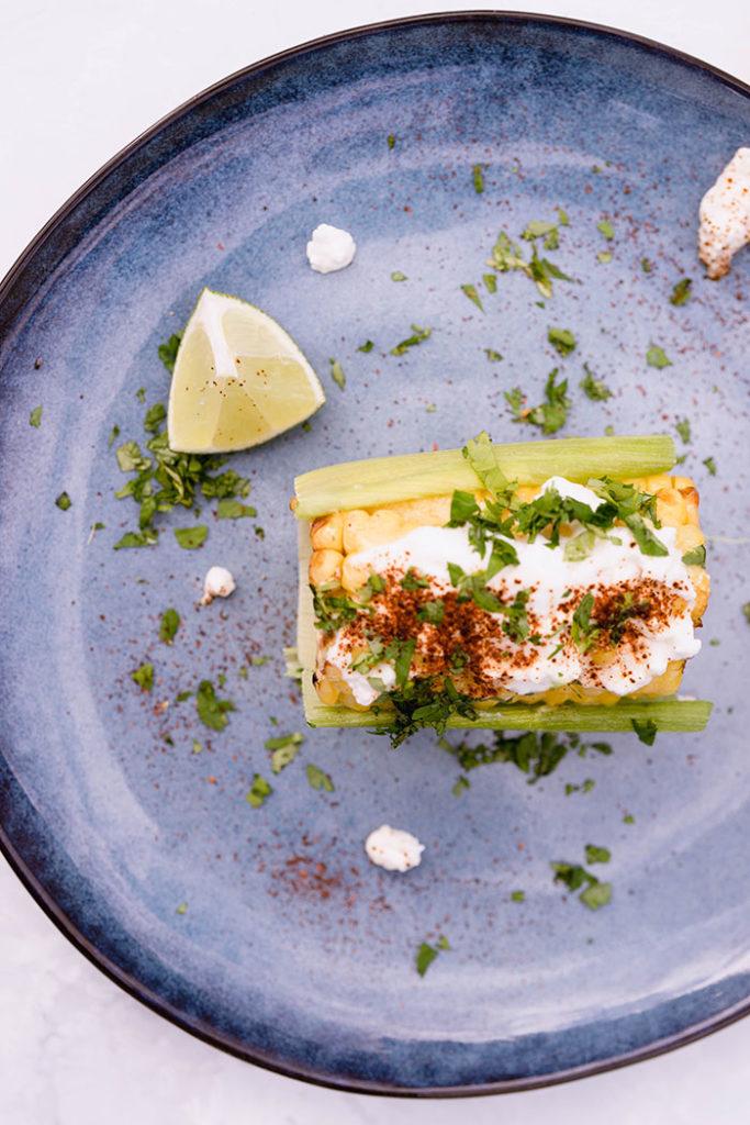 Elote sered with riccota, home made mayo and chili powder