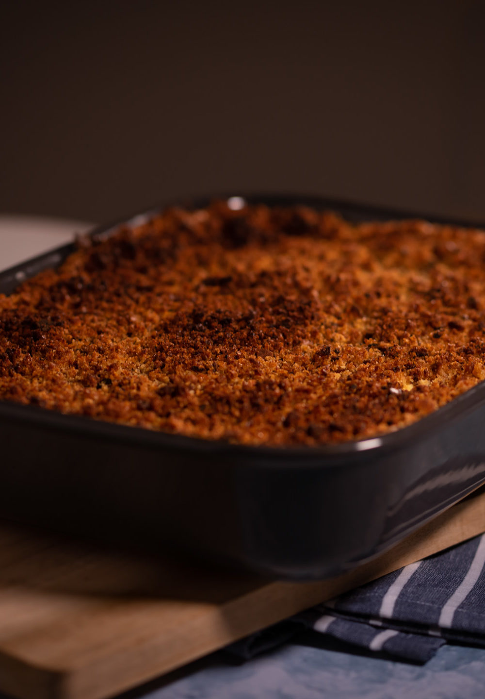 Fish pie in a pan placed on a wooden board